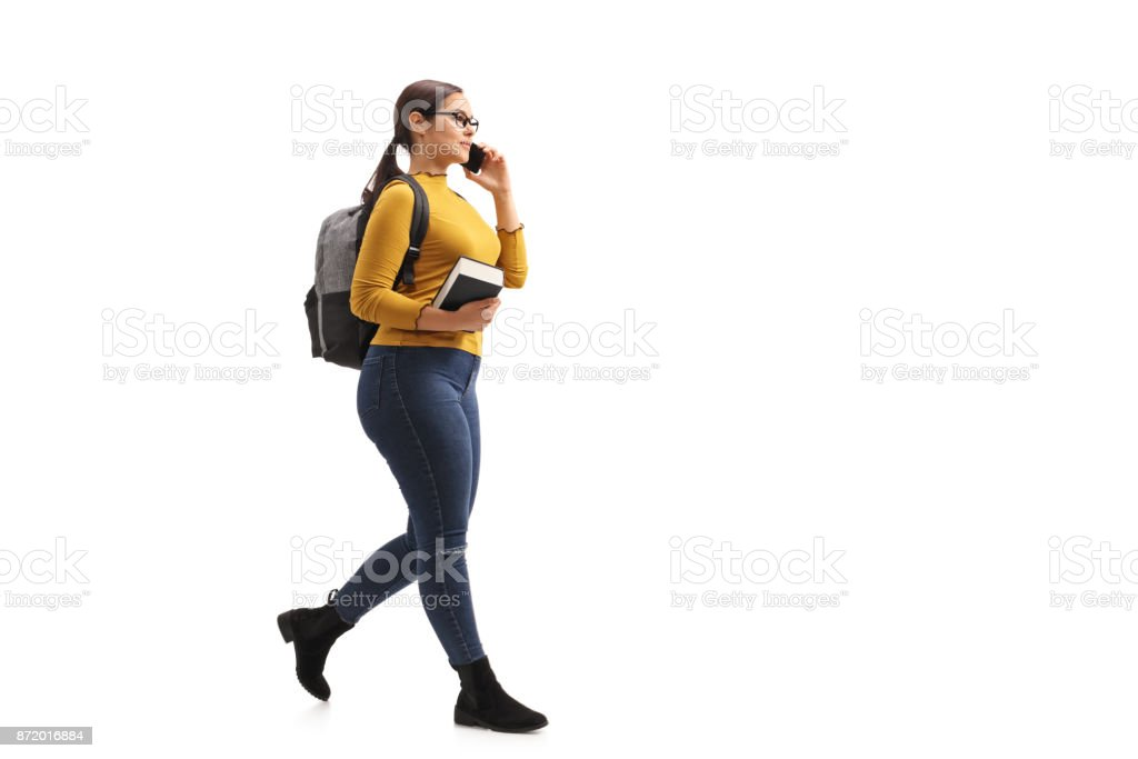 Female teenage student walking and talking on a phone stock photo