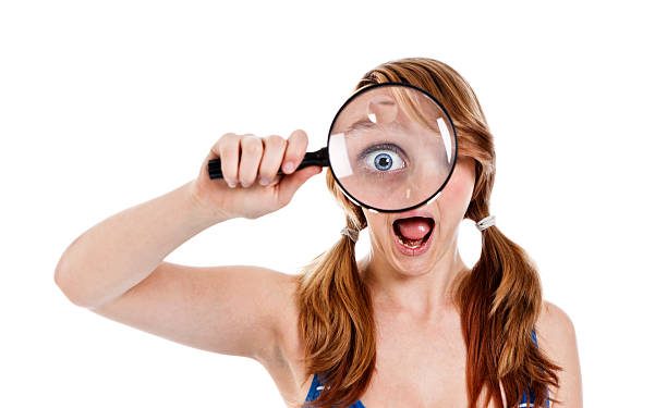 female teenager holding a magnifying glass to her eye - female spy stock photos and pictures