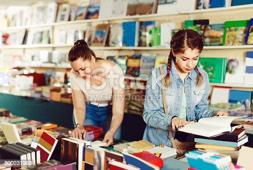 istock Female teenager is flipping books 800231968