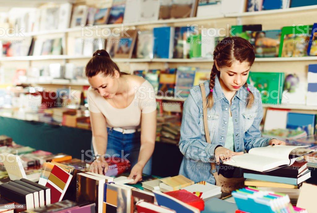 Female teenager is flipping books stock photo