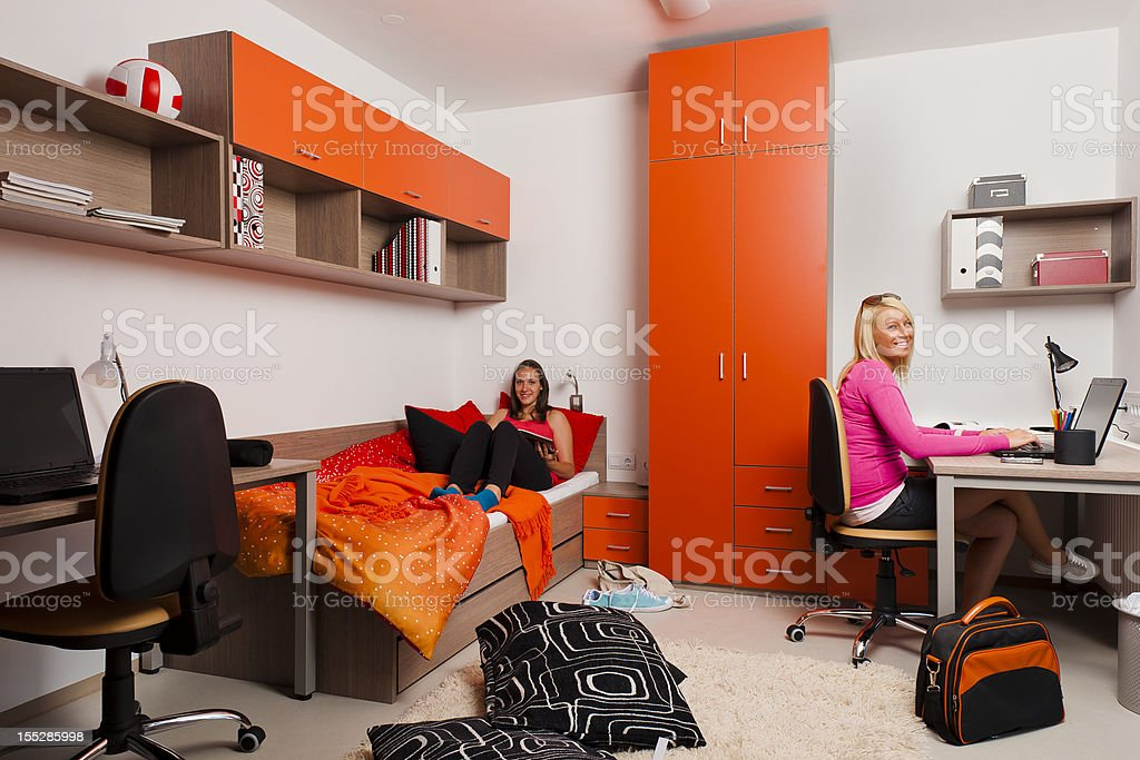 Female teenagers reading books and using the laptop stock photo