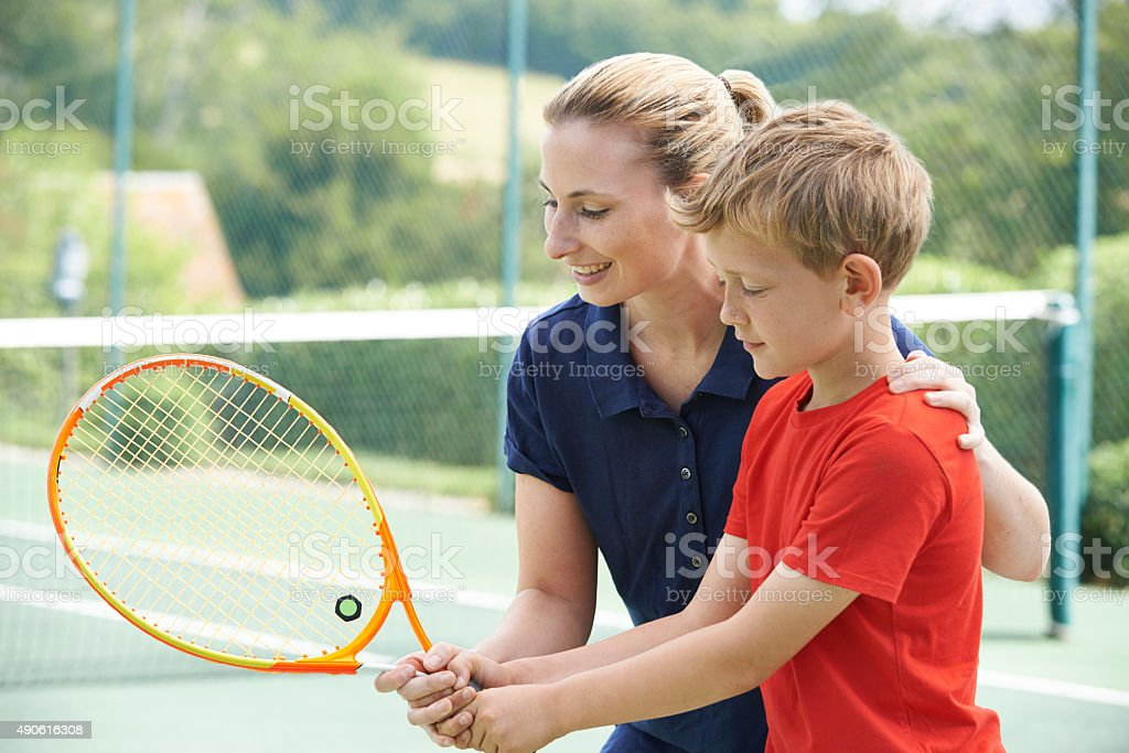 Female Tennis Coach Giving Lesson To Boy stock photo