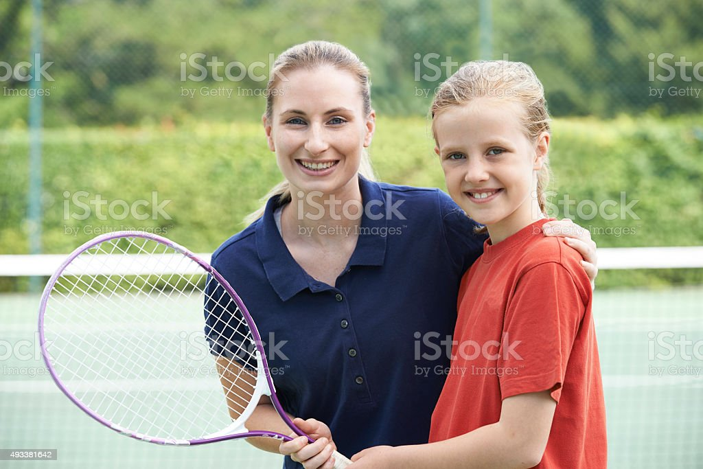 Female Tennis Coach Giving Lesson To Girl stock photo