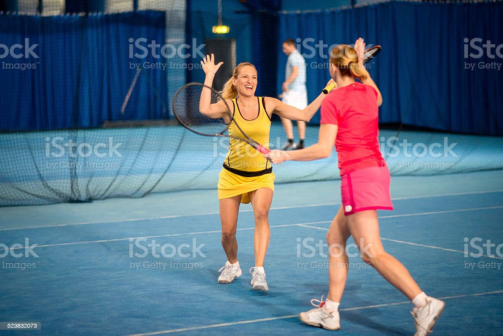 Female Tennis Co-players Giving a High Five stock photo