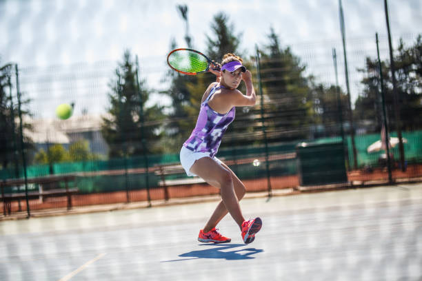 Female tennis player hits the ball with Backhand slice. stock photo