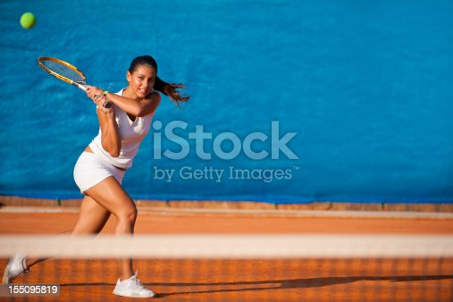 1153628111istockphoto Female tennis player hitting the ball 155095819