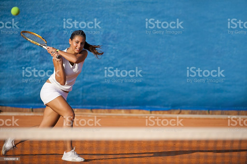 Female tennis player hitting the ball stock photo