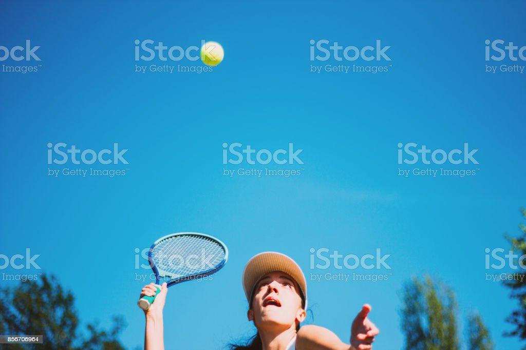 Female tennis player hitting the ball stock photo