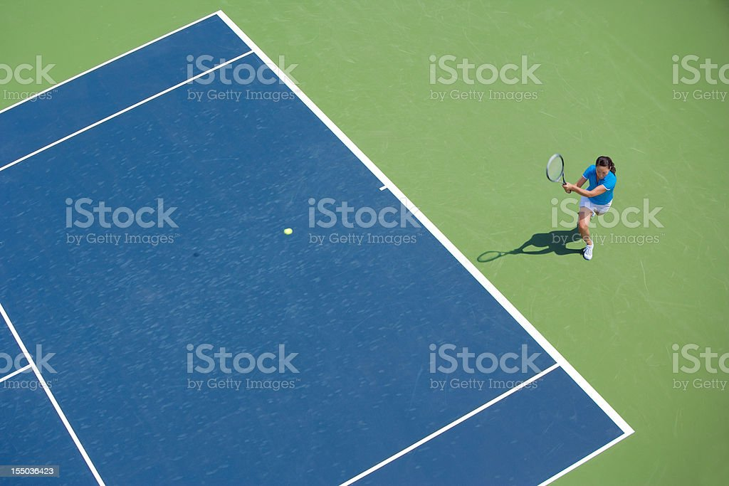 Female tennis player on blue and green court in middle of swing stock photo