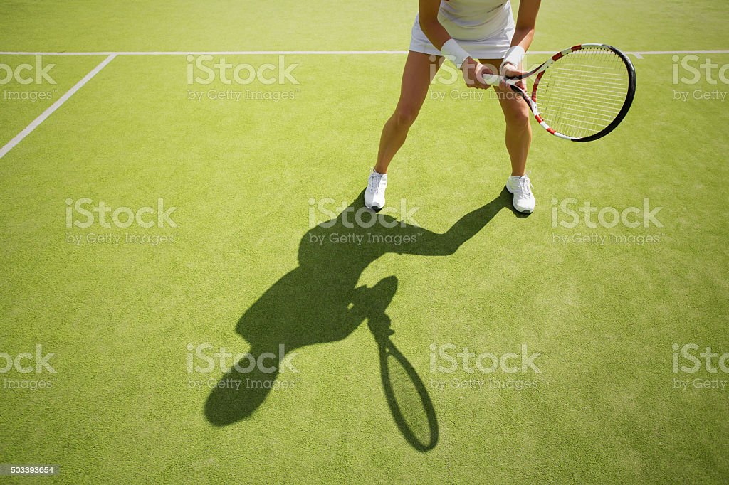Female tennis player on green court grass stock photo