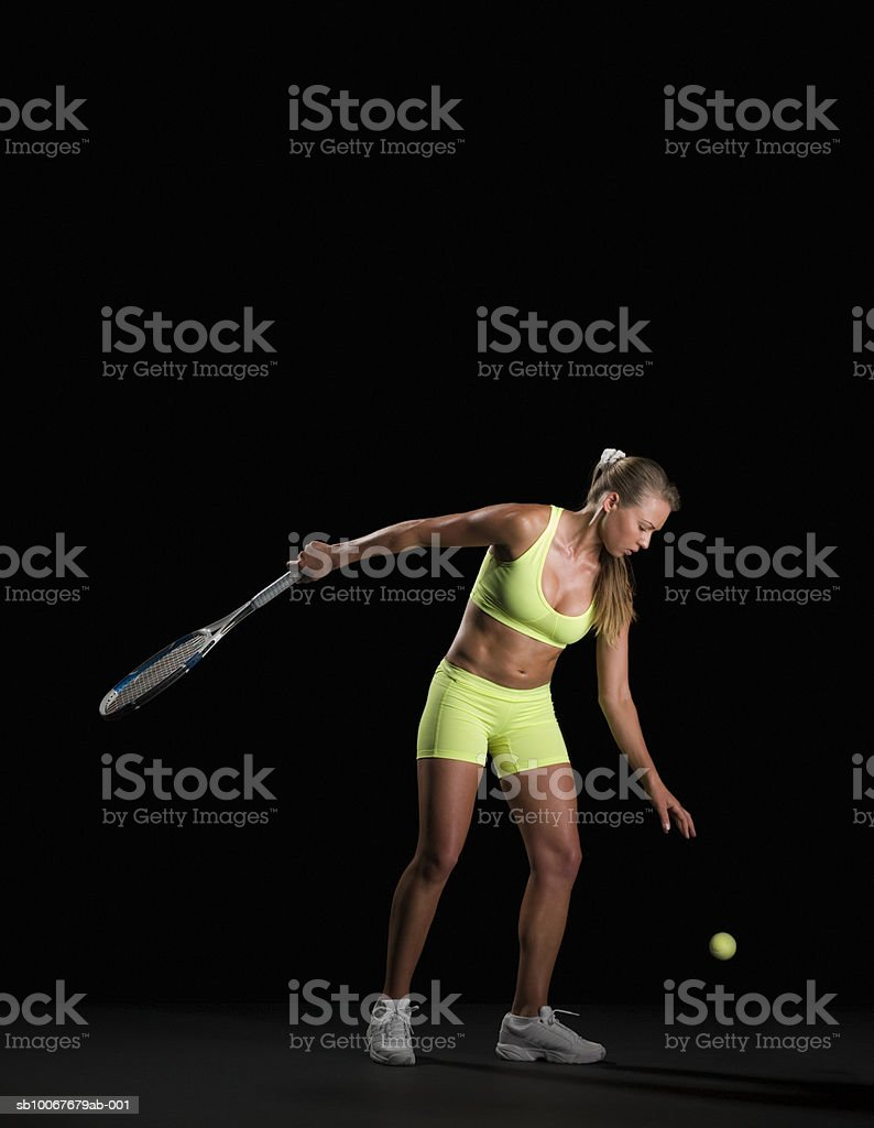 Female tennis player preparing to serve, studio shot 免版稅 stock photo