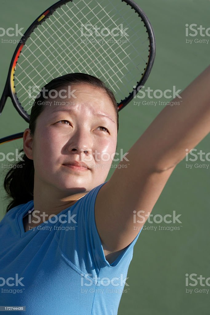 female tennis player serving with racket royalty-free stock photo