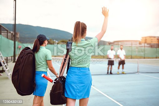 Female Tennis Players Waving To Their Male Opponents