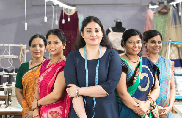 Female textile workers standing together in solidarity at factory stock photo
