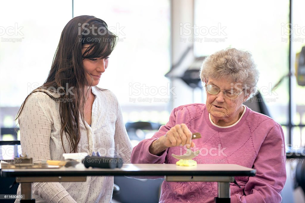 Female therapist assisting an elderly woman in a therapy session stock photo