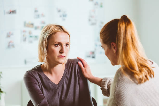 Female therapist consoling mid adult woman stock photo