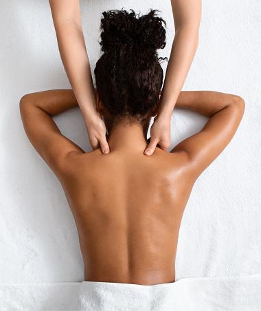 Female therapist massaging black woman neck, top view, spa concept