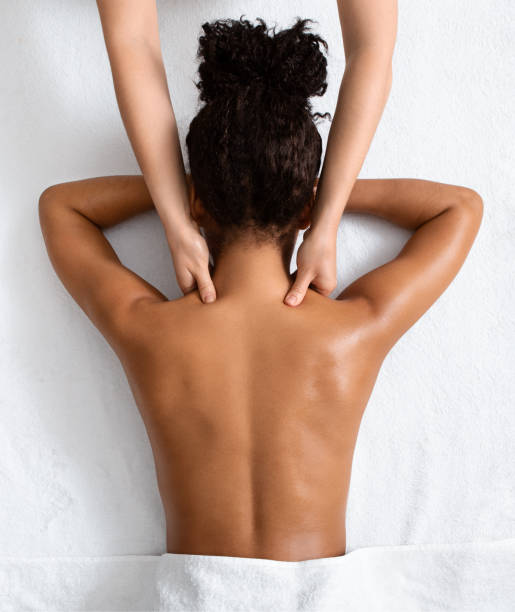 Female therapist massaging black woman neck, top view Female therapist massaging black woman neck, top view, spa concept massage stock pictures, royalty-free photos & images