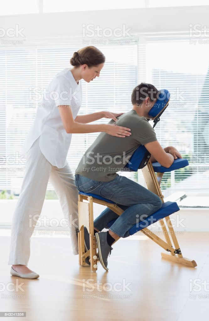 Female therapist massaging man in hospital stock photo