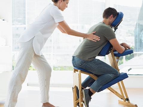istock Female therapist massaging man in hospital 843241410