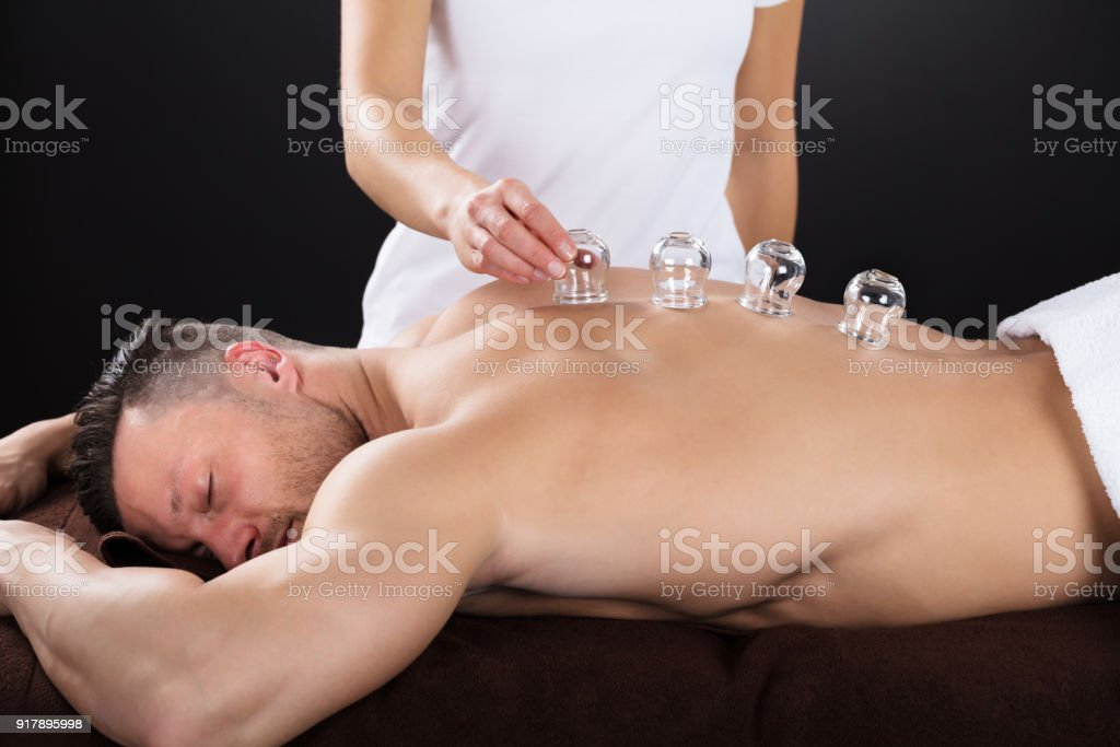 Female Therapist Placing Transparent Glass Cups On Man\'s Back In Spa