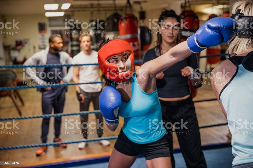 Female Throwing a Punch in the Boxing Ring stock photo