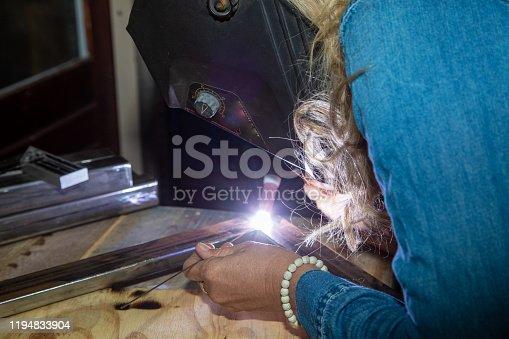 Female TIG welder welding steel