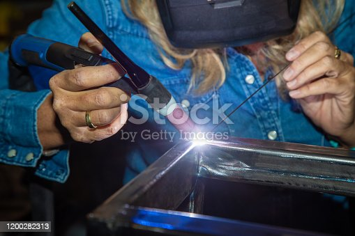 Female TIG welder welding steel