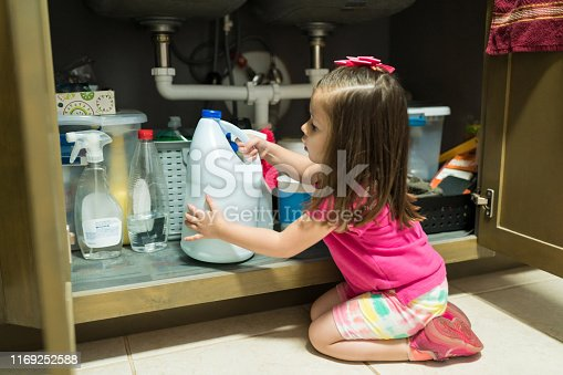 Little kid removing container from cabinet in kitchen at home