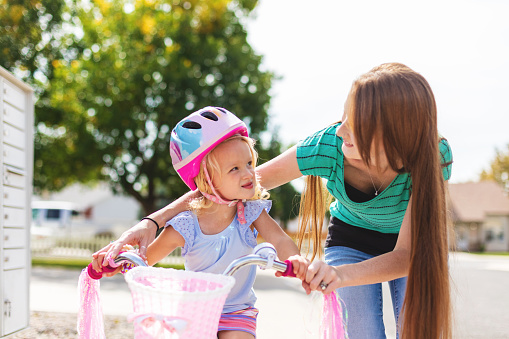 Female Toddler Riding a Bicycle with help from Her Mother