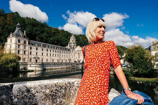 Attractive female tourist across from the Benedictine Abbey at Brantome in the Dordogne region of France.