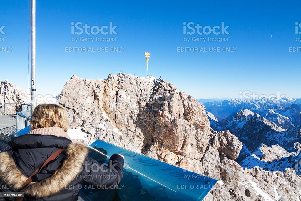 Female tourist at information board on Zugspitze stock photo