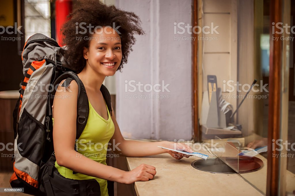 Female tourist buys a ticket at terminal station ticket counter stock photo