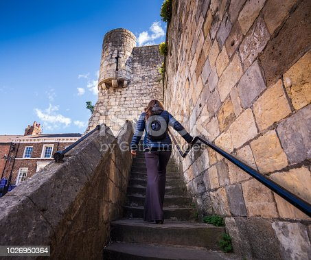 The woman is climbing up some stairs to explore the stone fortified walls, which surround the historic English city. She's traveling alone in the UK.