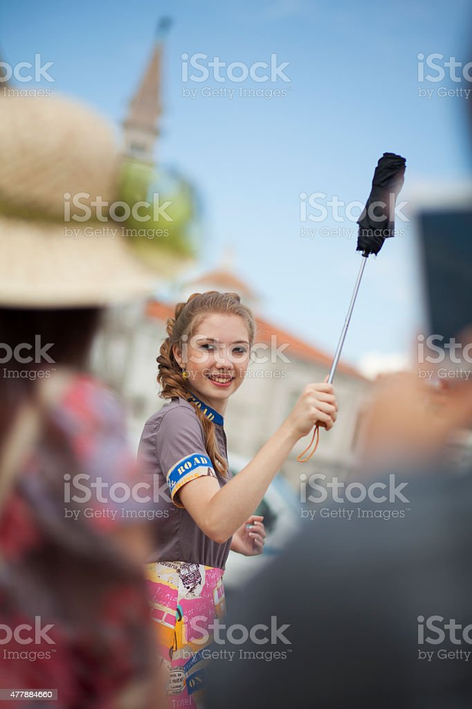 Female tourist guide with umbrela in an old city center. stock photo