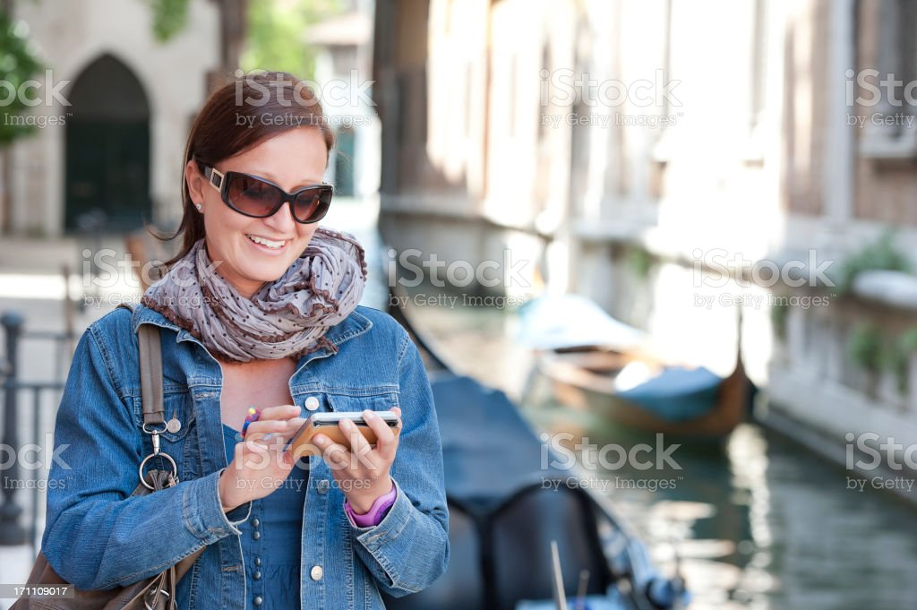 Female tourist in Italy with smartphone next to a canal royalty-free stock photo