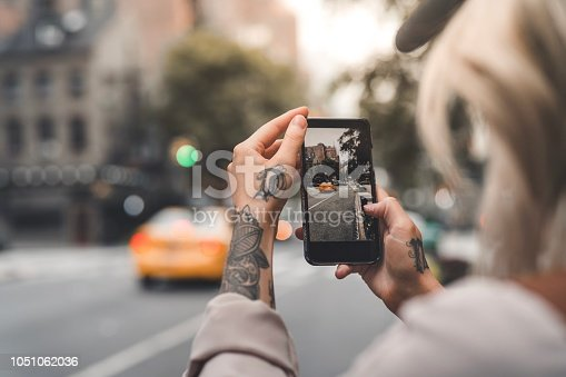 A tattooed woman is a tourist in New York, taking photos with her smart phone.