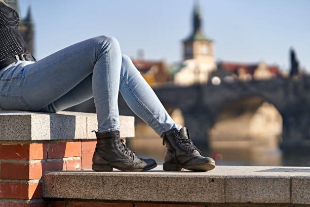 Female tourist in Prague Close-up of a female traveler sit down on a stone wall and dressing casual jeans and to and old style leather black boots with a blurred background of the Bridge of Charle in Prague. Holidays concept. skinny jeans stock pictures, royalty-free photos & images
