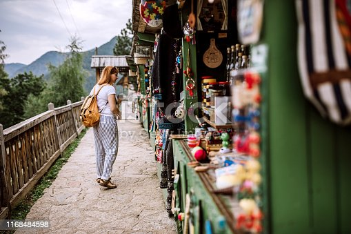 Young Female tourist looking for souvenirs on street market on her summer vacation