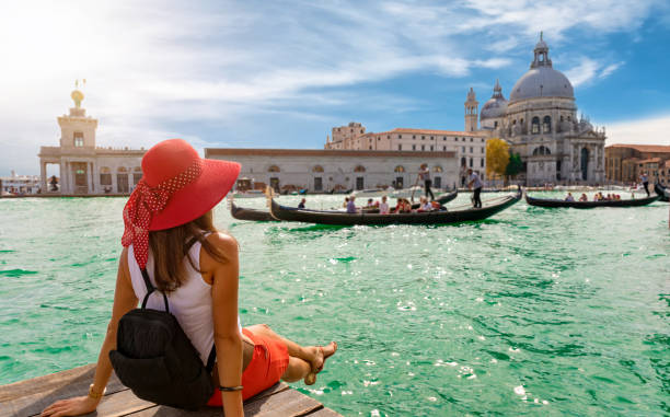 female tourist looking the basilica di santa maria della salute and canale grande in venice, italy - vacanze foto e immagini stock