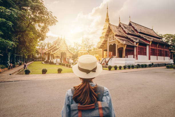 Female tourist looking to the beautiful view of Wat Phra Singh in Chiang Mai, Thailand at sunset. One of the best examples of classic Lanna style architecture in Chiang Mai province of Thailand. chiang mai province stock pictures, royalty-free photos & images