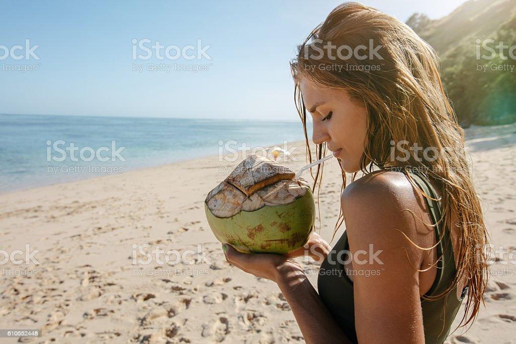 Female tourist on beach vacation with coconut - foto de acervo