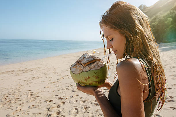 Female tourist on beach vacation with coconut - foto de acervo