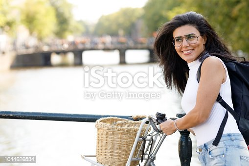 Female Cyclist Enjoying Amsterdam Canal View while on holiday in The Netherlands