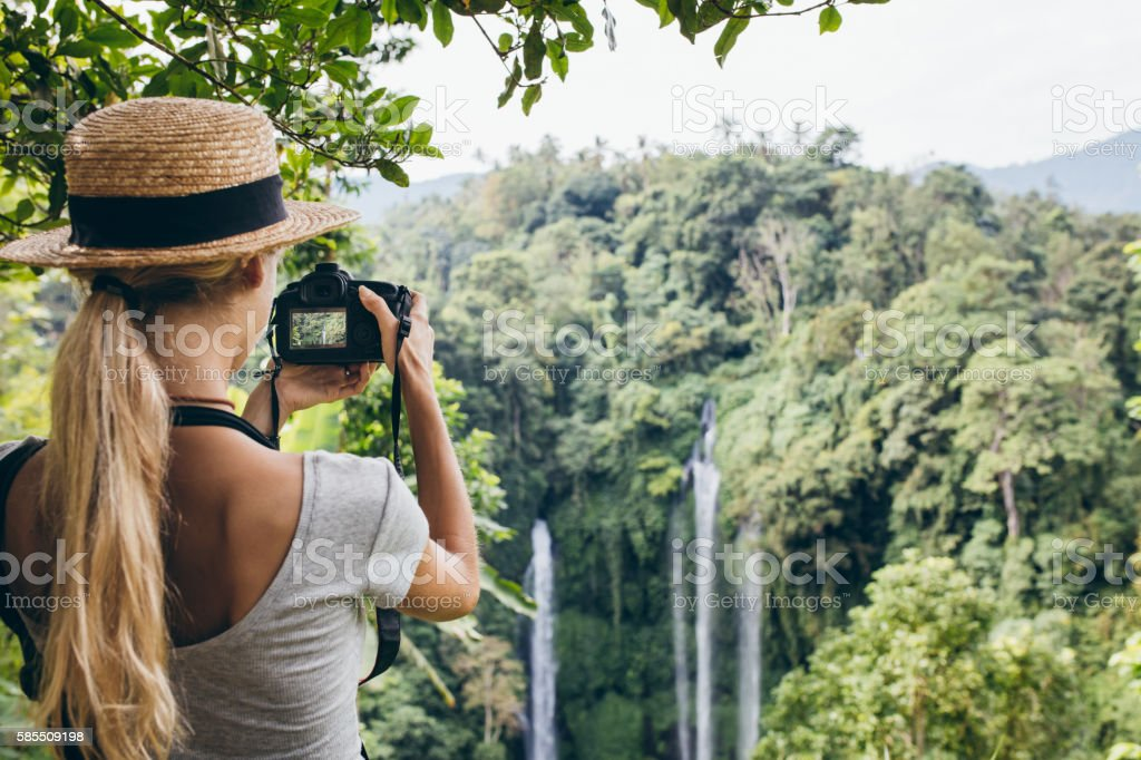 Female tourist photographing a waterfall in forest stock photo