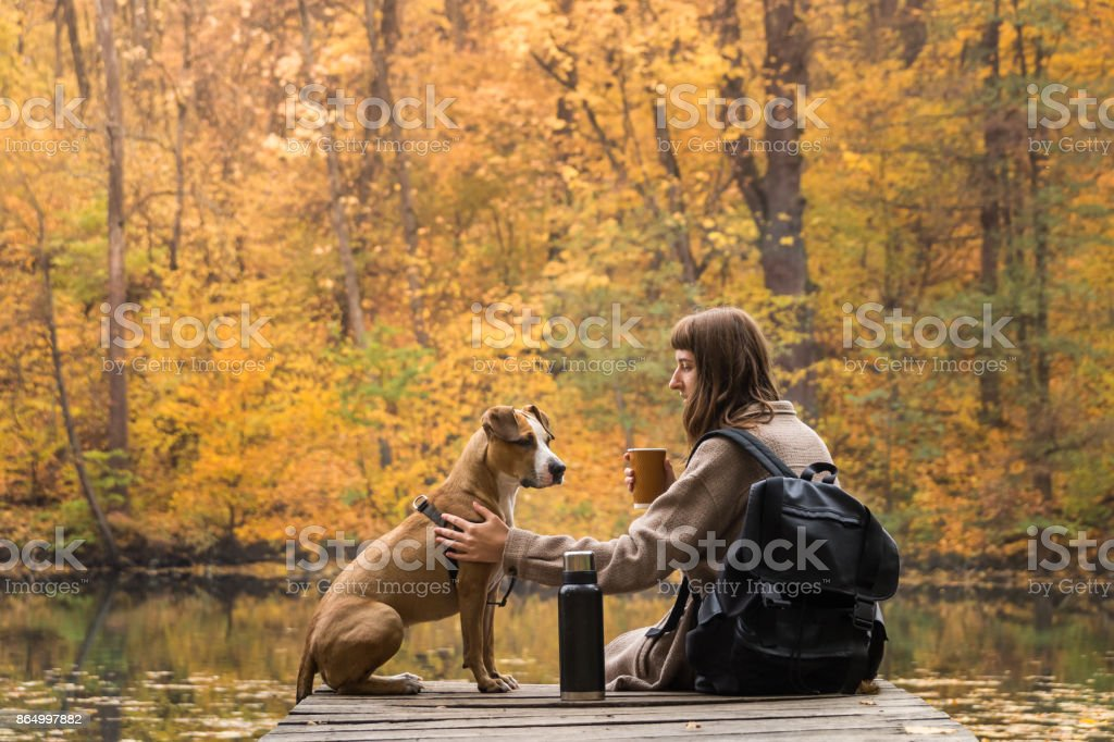 Female tourist sit with dog near lake and enjoy beautiful autumn view drinking cup of coffee stock photo