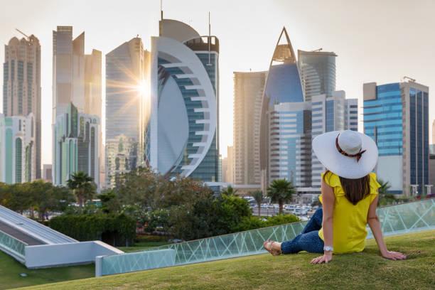 turista se sienta en un parque delante del skyline de doha, qatar - qatar fotografías e imágenes de stock