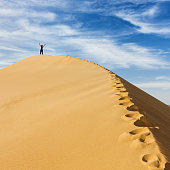 Young female standing  the top of sandune. The Sahara Desert is the world's largest hot desert with the biggest sand dunes.