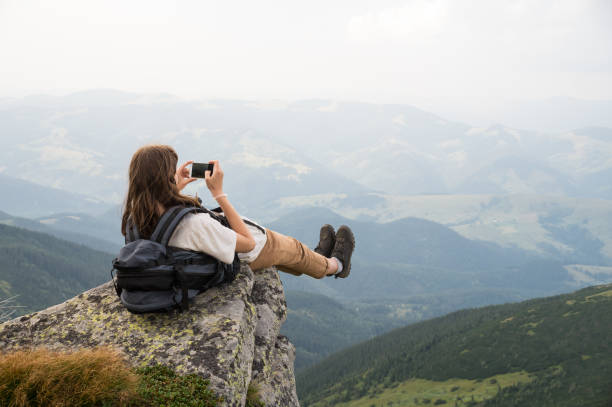 female tourist takes photo of legs with cell phone from top of the mountain cliff - danger stock pictures, royalty-free photos & images