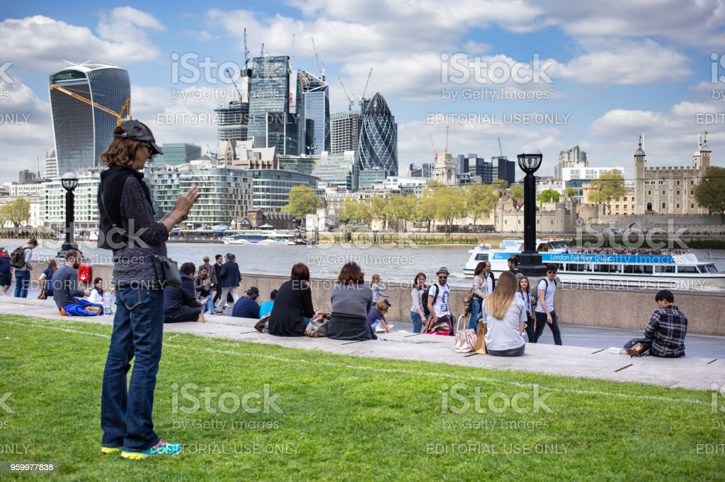 Female tourist taking a picture of the London skyline around the London Riverside area near Potters Fields Park with the famous Walkie-Talkie building on the horizon stock photo